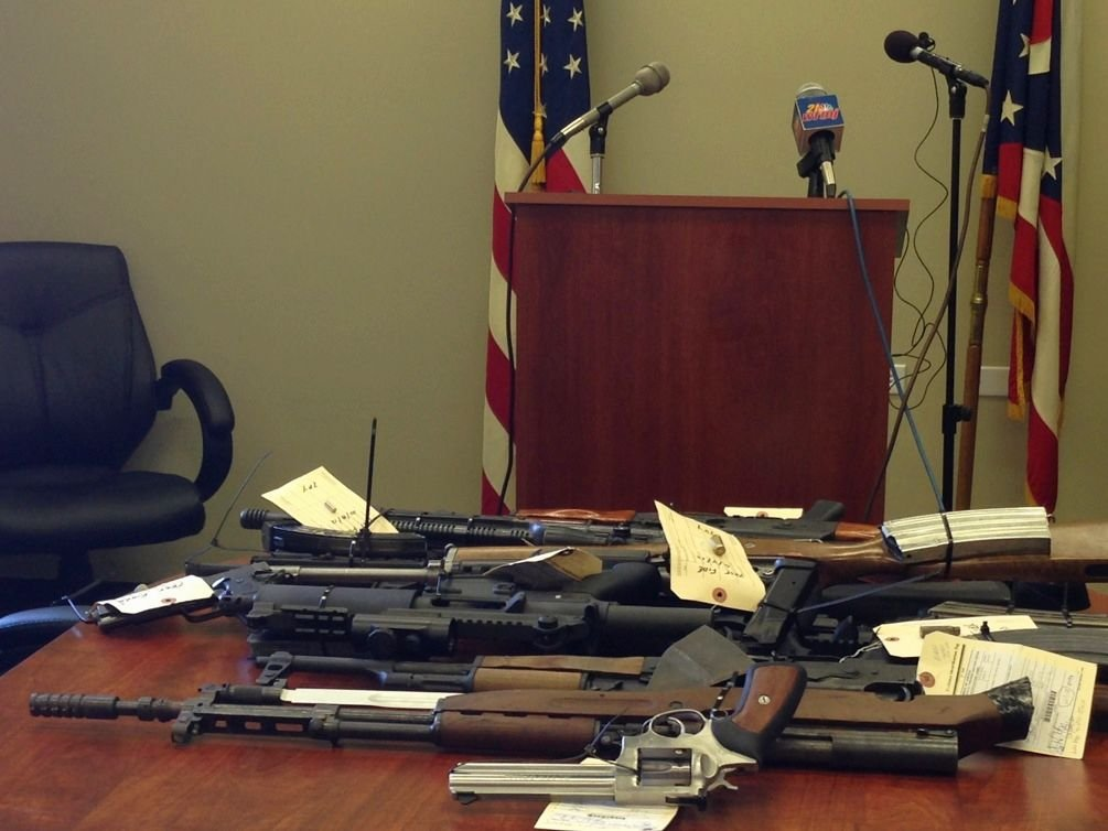 Officials display some of the confiscated guns discovered during the investigation.