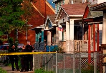 (AP Photo/Plain Dealer, Scott Shaw). Cleveland Police stand outside a home where they say missing women, Amanda Berry, Gina DeJesus and Michele Knight were found in the 2200 block of Seymour Avenue in Cleveland on Monday, May 6, 2013.